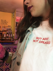 female takes a selfie while wearing a white swearing is cool and little big art buy art not drugs tshirt while in a bar