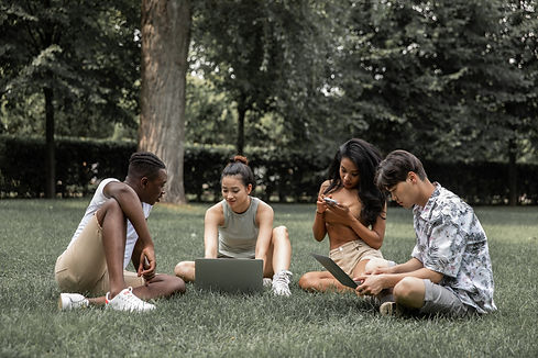 pexels-monstera-5384517 students sitting on the grass with smartphones and computers