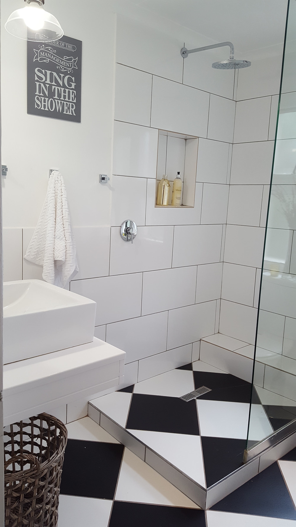 This bathroom makes use of both an over-sized metro wall tile and large floor tiles to create diagonal lines, both of which make the space feel bigger. The black and white creates interest and echoes and classic look