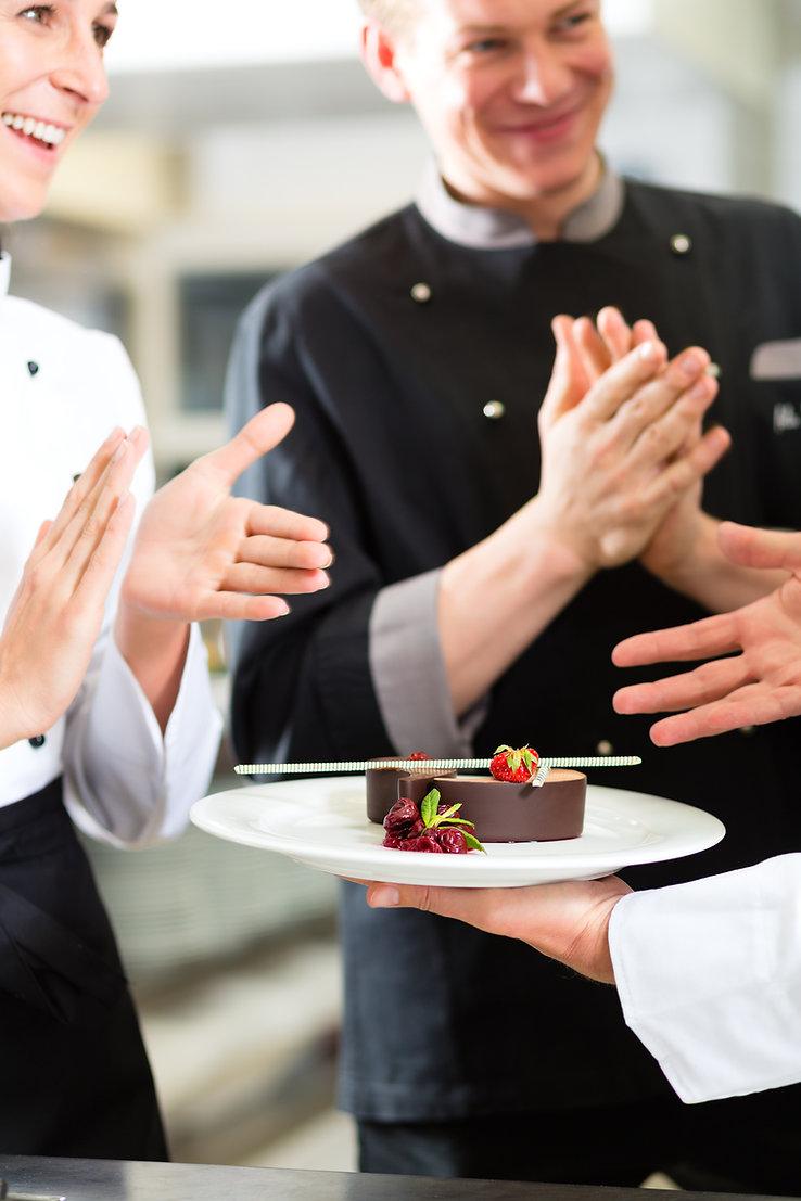 Chef team in restaurant kitchen with des