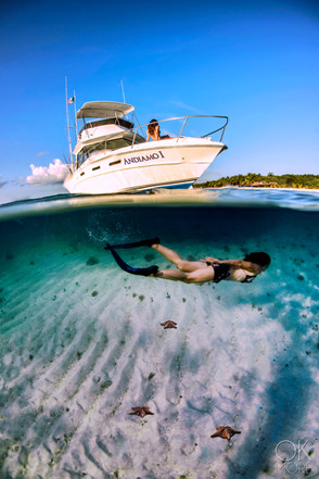 Commercial photography: split shot underwater leisure boat in the caribbean ocean, woman swimming