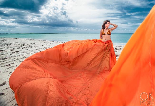 Portrait of woman on the beach with orange parachute dress, Cozumel, Mexico