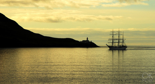 Travel photography destination Shetland island, Scotland, landscape, tall ship by lighthouse at sunrise, golden hour lerwick