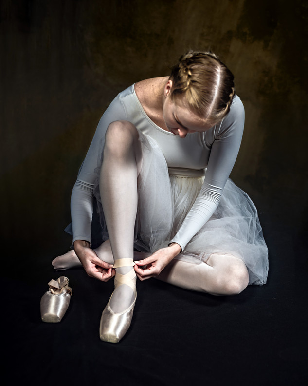 Dancer tying her pointe shoes
