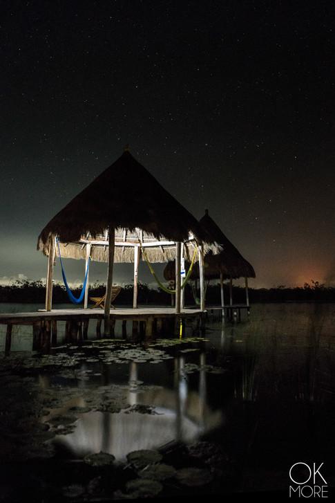 Night photography, stars over Mahahual lagoon and palapa reflection