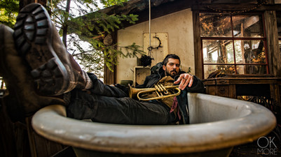 Travel photography destination California: musician portrait, trumpet player in the cabin in the woods
