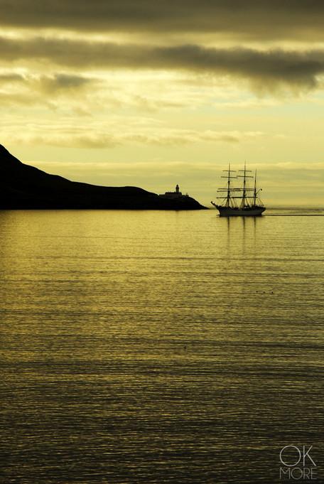 Travel photography destination Shetland island, Scotland, landscape, tall ship by lighthouse at sunrise, golden hour lerwick