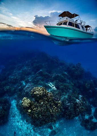 Commercial photography: Underwater caribbean ocean, mesoamerican barrier reef, split shot of leisure boat at sunset
