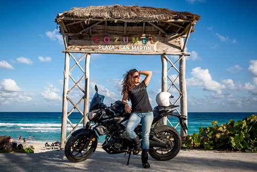 Commercial portrait: motorcycle and biker girl by the ocean
