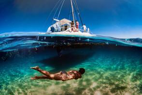 Commercial photography: split shot underwater catamaran sailing in the caribbean ocean, woman swimming