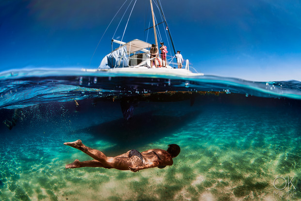 Commercial photography: split shot underwater catamaran sailing in the caribbean ocean, woman swimming