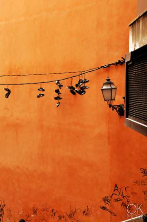 Street photography: Palma de Mallorca, Spain, shoes on a cable against orange wall