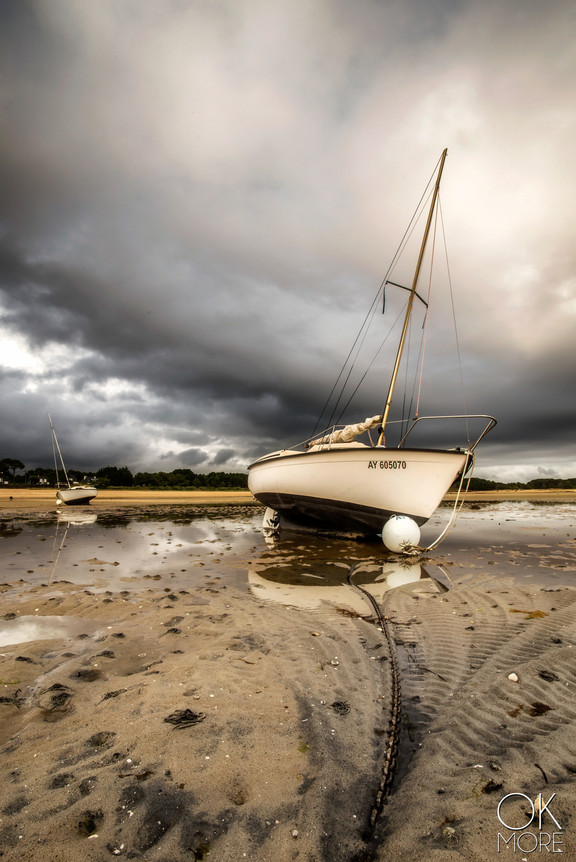 sailboat at low tide, reflections and stormy skies in Bretagne, France