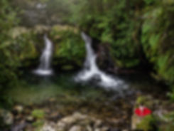 woman in red dress sits by a waterfall in Villarrica, Chile