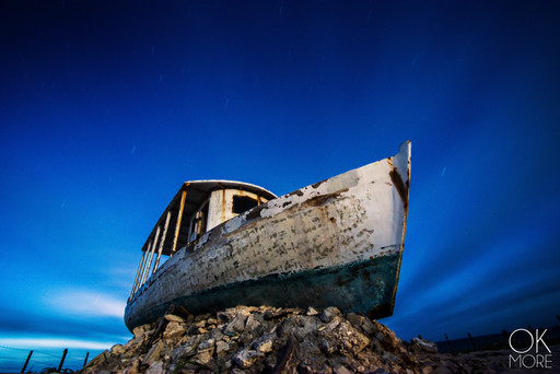 Landscape photography: night shot of old abandoned stranded fishing boat