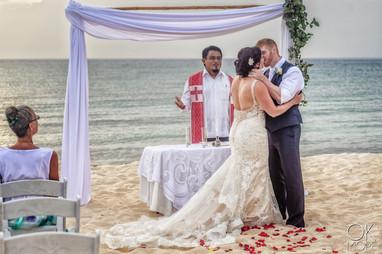 Wedding photography: ceremony kiss, altar on the beach, caribbean ocean