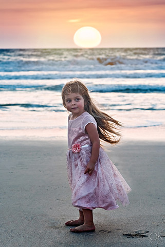 Child portrait, girl on the beach at sunset
