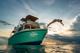 Commercial photography: leisure boat at sunset, woman diving in caribbean ocean