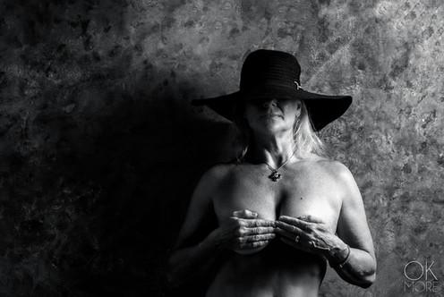 Fine art portrait, woman wearing a hat in black and white, studio