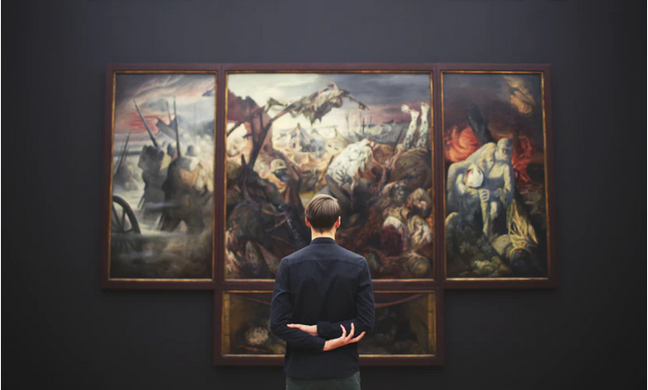Man looking at classical art with his back turned to the camera. Image credits: Unsplash
