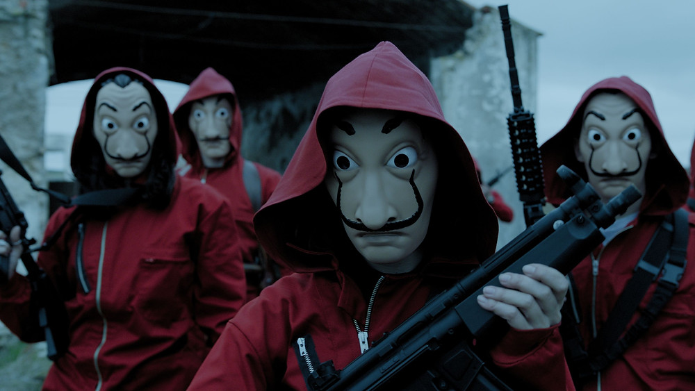 A still from Money Heist (La Casa de Papel) showing the robbers dressed in red overalls and Salvador Dali masks