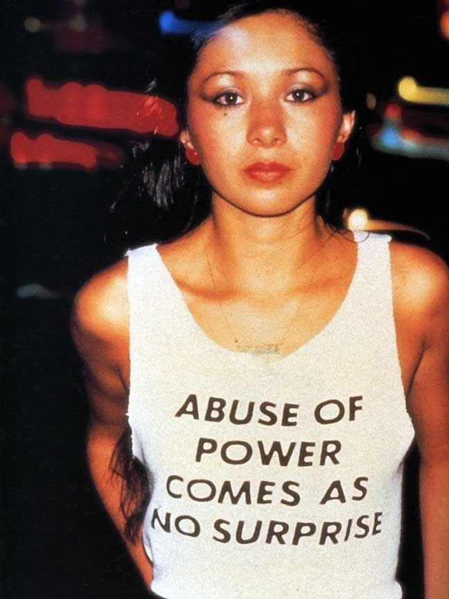 'Abuse of Power Comes As No Surprise' from the series 'Truisms'. Jenny Holzer.  T-shirts,1980-, worn by Lady Pink © 1983 Lisa Kahane, NYC.   Image credits: Tate Museum.