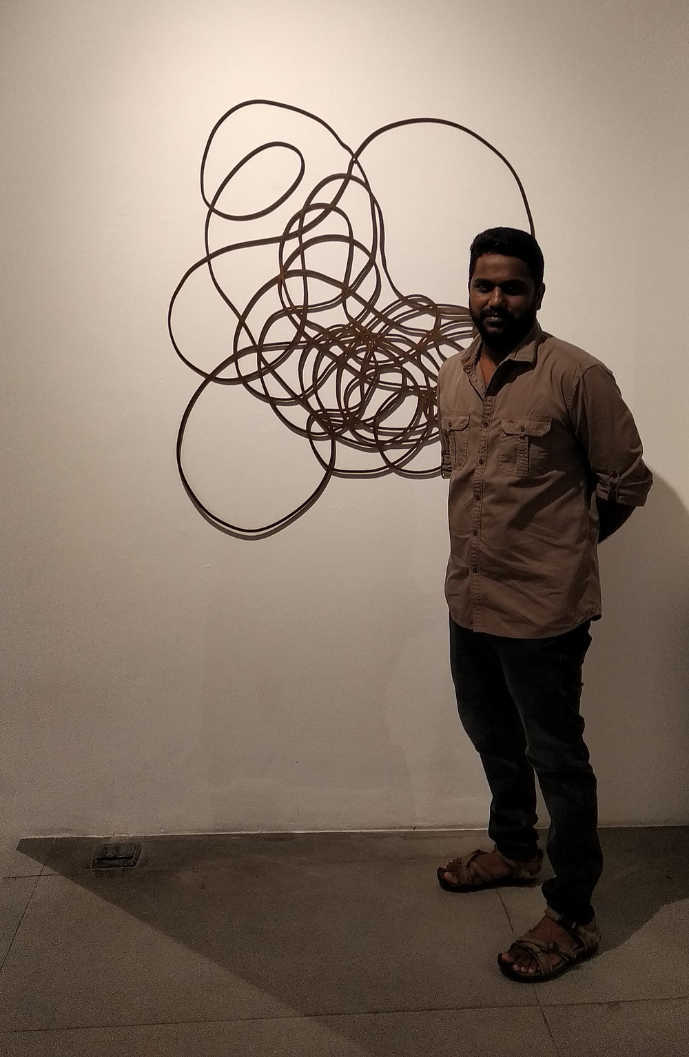 Kumaresan Selvaraj alongside his wall sculpture, 'It Ends Where it Starts'