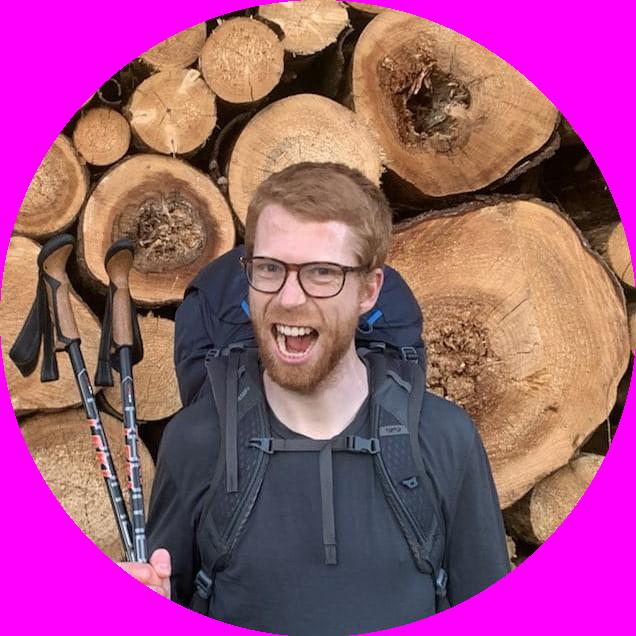 Primeiro mit Wanderstöcken vor einem Stapel Holz