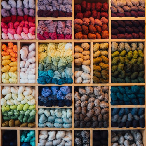 Wall of different colored yarn skeins.