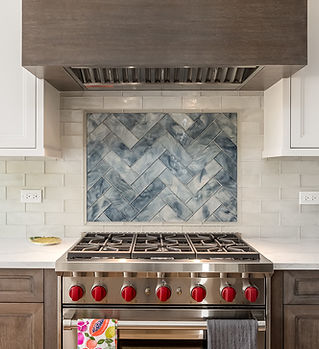 "36"" Wolf Range with Red Knobs in two toned Kitchen with blue and white backsplash"