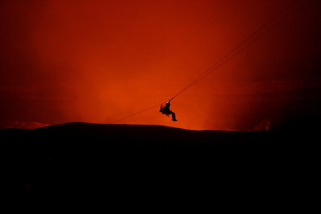 Silhoutte of zipline over volcano smoke