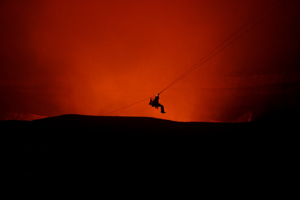 Silhoutte of zipline over volcano smoke