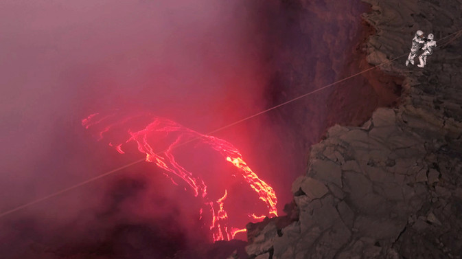 Incredible shot of two people on the cliff of a volcano about to zipline