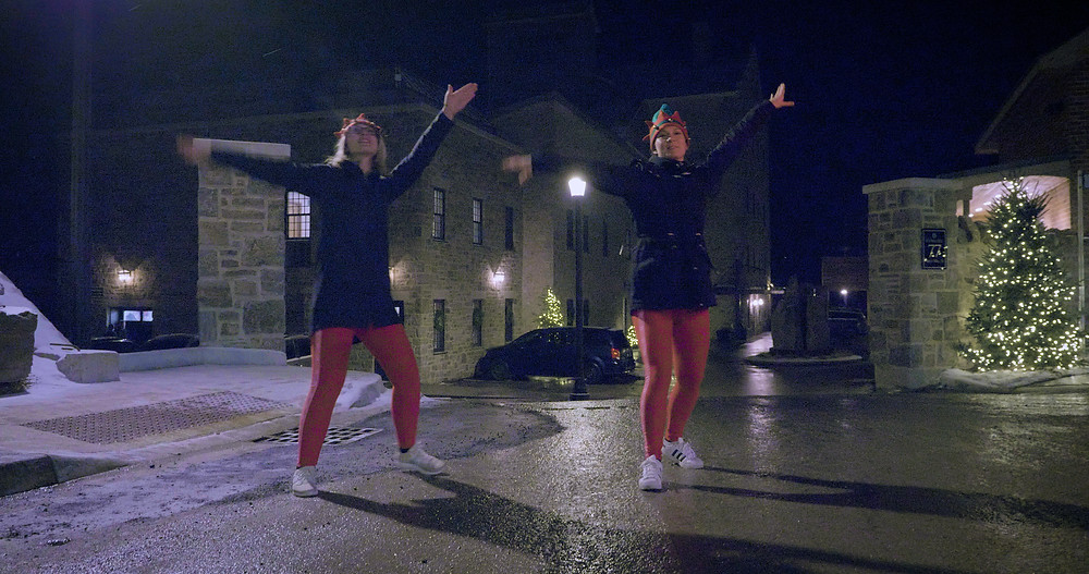 Two dancing elves in front of the Elora Mill in downtown Elora Ontario on a wintery evening