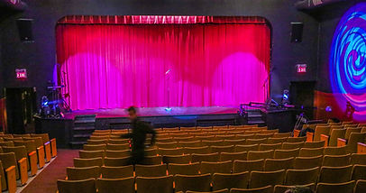 Fergus Grand Theatre auditorium facing stage and stae curtains.  Empty seats with an audio technician walking past