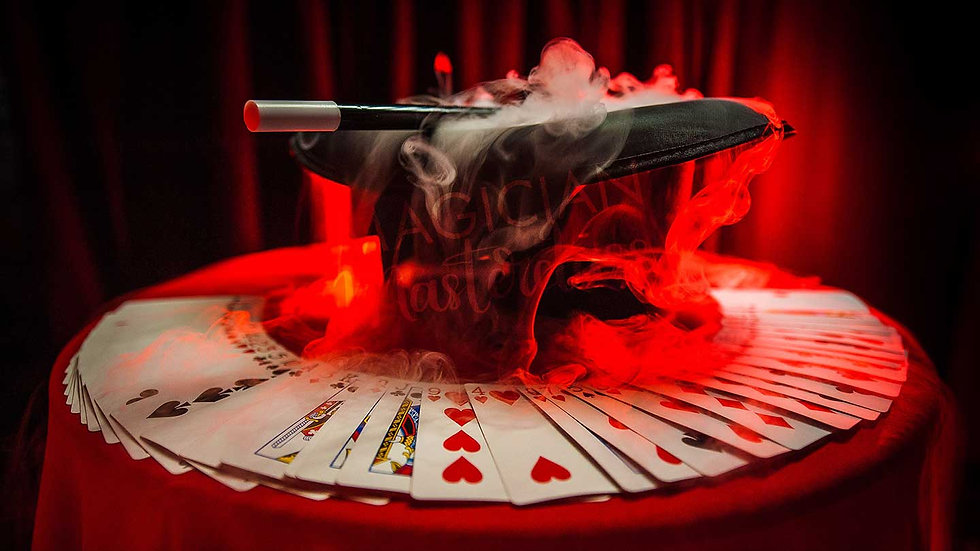 Magician Top Hat, Magic Wand and Playing Cards spread on a magician table