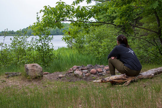 Sociologist Stephanie Wilson wearing Kompass Apparel while sitting at a campsite in Chequamegon-Nicolet National Forest