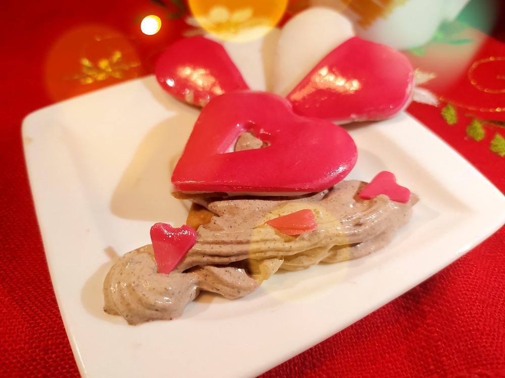 biscotti a forma di cuore di san valentino, con farcitura di crema e panna e decorazioni di ghiaccia reale e pasta di zucchero
