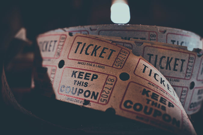 A close up color image of an old roll of tickets. Overlaid in white capital letter the words: Tickets 2021.