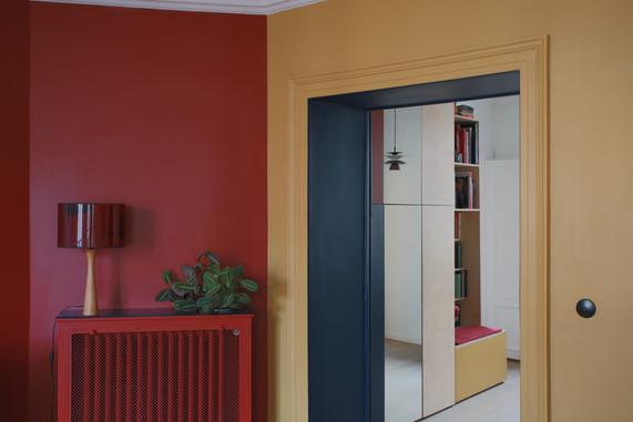 Vue depuis le salon du meuble d'entrée conçu sur mesure et reprenant le jeu de couleurs, fil conducteur dans tout l'appartement