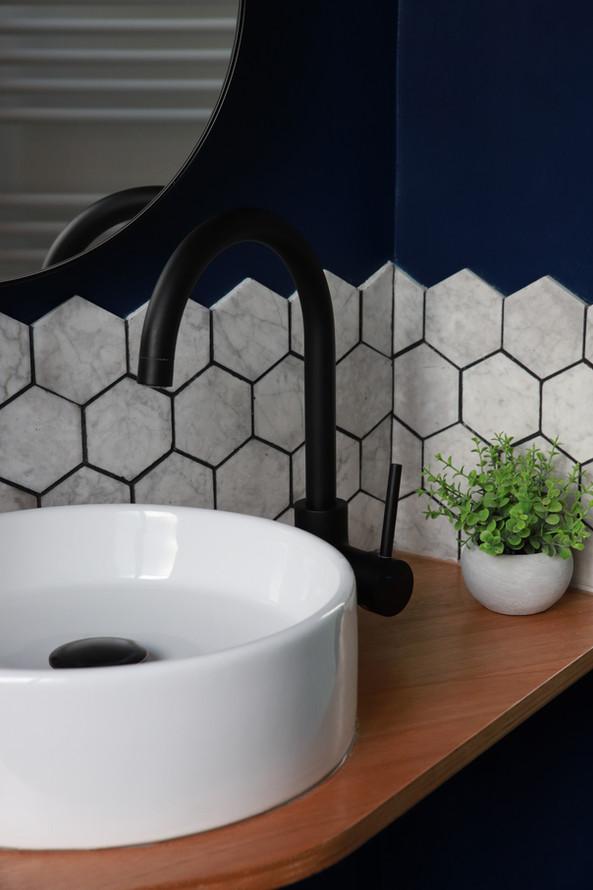 Détail de la salle de douche de la suite parentale ou se mêle marbre, bois, céramique et éléments de robinetterie noir mat