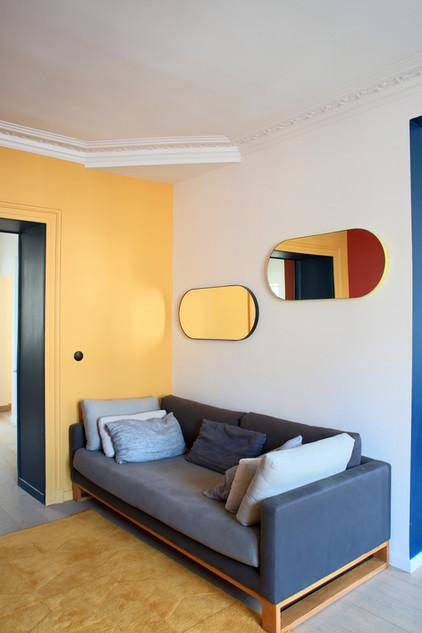 Vue du salon et des jeux de géométries entre les miroirs, les moulures, le canapé et le tapis en relief