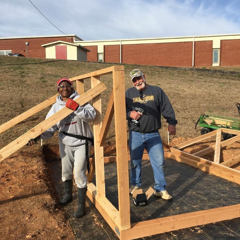 farm volunteers building greenhouse