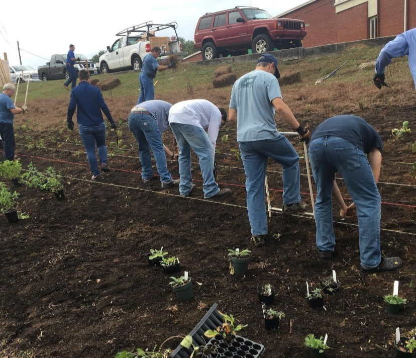 volunteers farm planting the pollinator garden