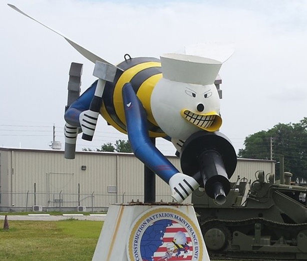 Photo of a SeaBee sculpture located in front of a building and heavy equipment at the Jacksonville Construction Battalion Maintenance Unit