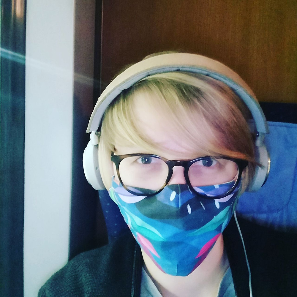 Anne sitzt mit Mundschutz in der Bahn