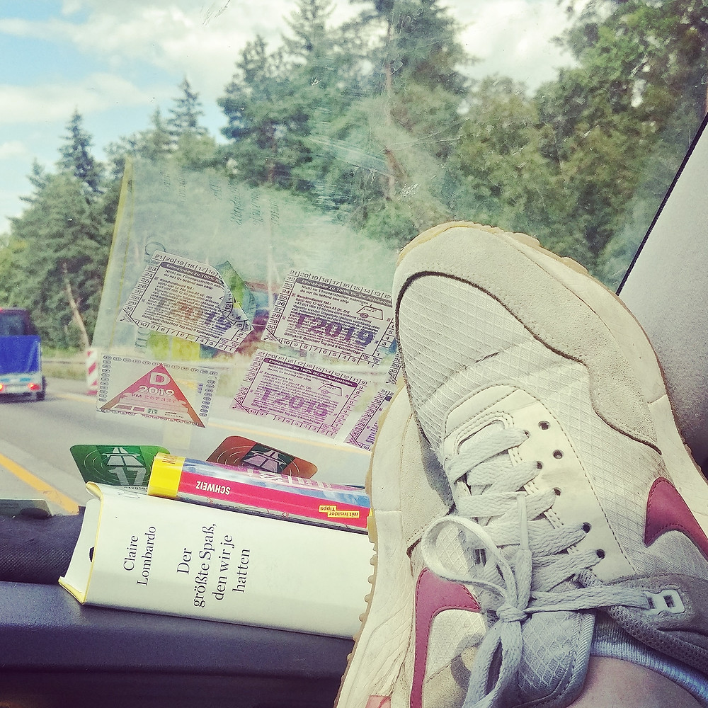 Die Füße von Anne auf dem Armaturenbrett im Auto