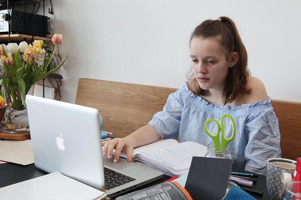 Jugendliche sitzt vor dem Laptop und lernt