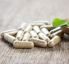 Herbal capsules with moringa leaf on woo
