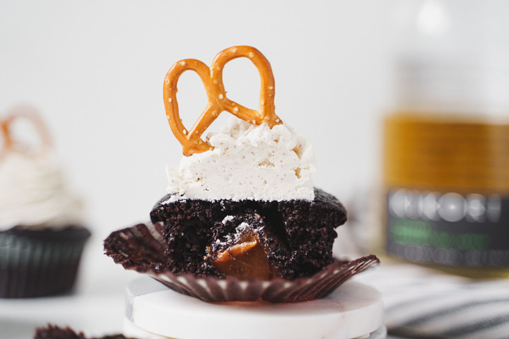 chocolate cupcake with caramel center, buttercream frosting and pretzel decoration